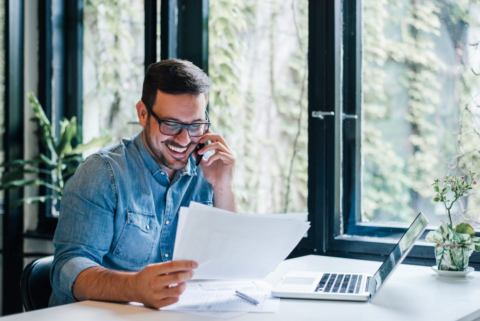 Portrait Of Young Smiling Cheerful Entrepreneur In Casual Office Making Phone Call While Working With Charts And Graphs Looking At Paper Documents