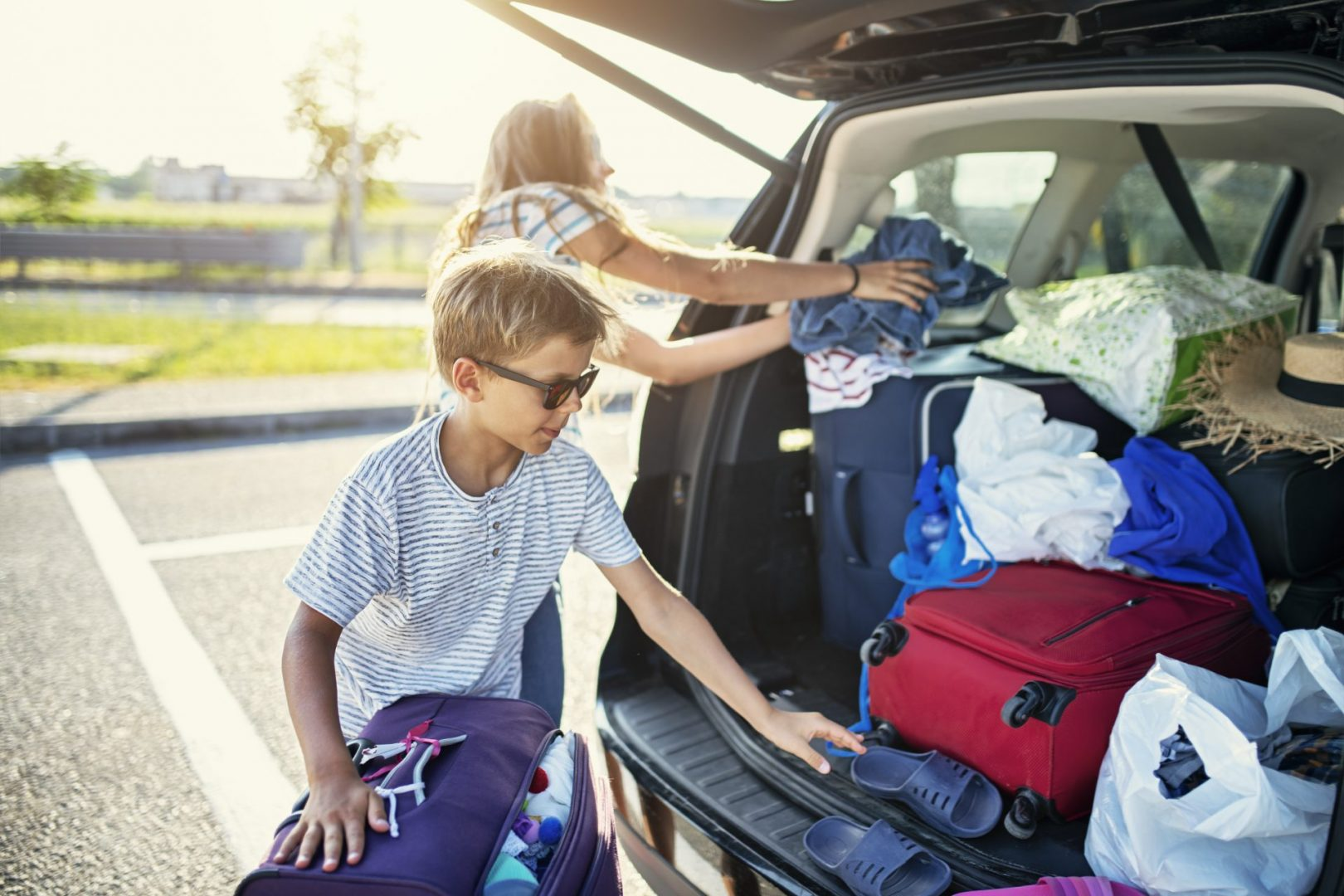 Kids Helping To Pack The Family Car For Road Trip.