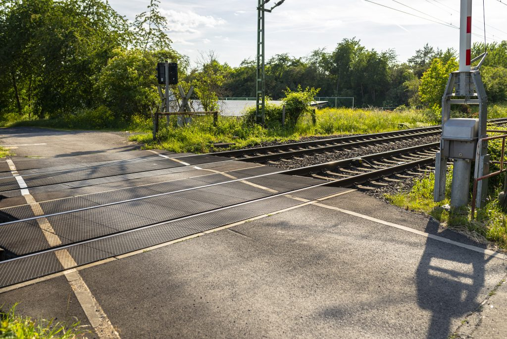 Empty Railroad Crossing In The Countryside, On The Road With Open Barriers.